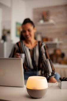 Vrouw geniet van aromatherapie terwijl ze op een laptop in de keuken werkt