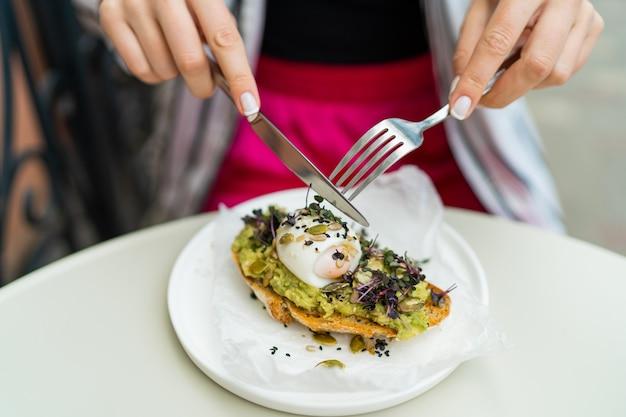 Vrouw geniet van avocadotoost in café tijdens het ontbijt.