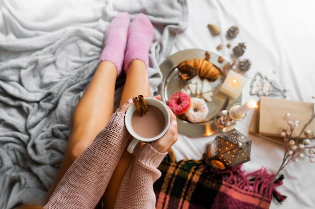 Vrouw geniet van de ochtendtijd in haar bed, met warme, gezellige wollen trui en roze sokken, met grote kop koffie.