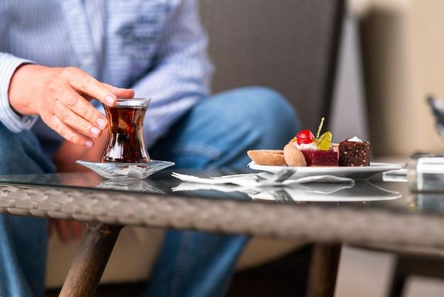 Vrouw geniet van een glazen mok hete zwarte thee met gebak