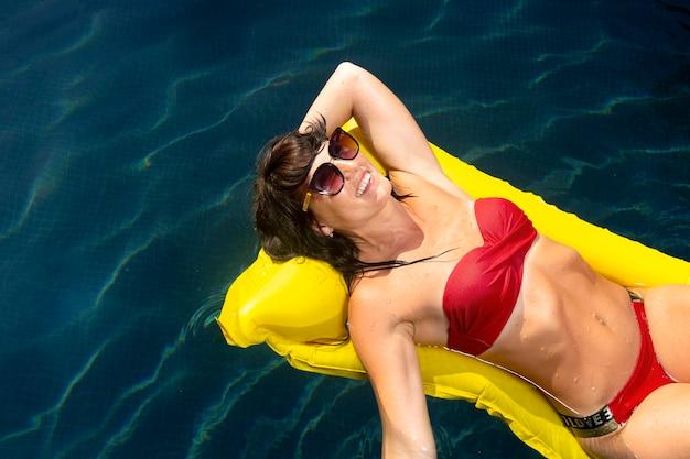 Vrouw geniet van haar dag bij het zwembad op poolvlotter