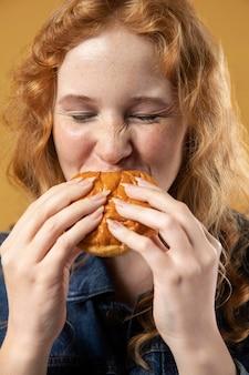 Vrouw geniet van het eten van een hamburger