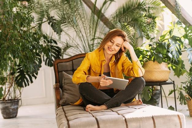 Vrouw geniet van het gebruik van digitale tablet voor online winkelen of het lezen van social media nieuws in serre tuin thuis