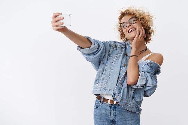 Vrouw geniet van het nemen van selfie op nieuwe smartphone, aanbiddende camera en perfect licht voor goede foto poseren gelukkig lachend, vreugdevolle hand met mobiele telefoon uitstrekken om rechte hoek over witte muur te krijgen