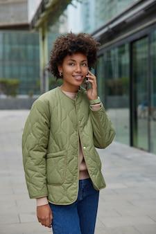 Vrouw geniet van positief mobiel bellen glimlacht aangenaam kijkt in de verte draagt casual outfit loopt in stedelijke omgeving tevreden met goedkope tarieven