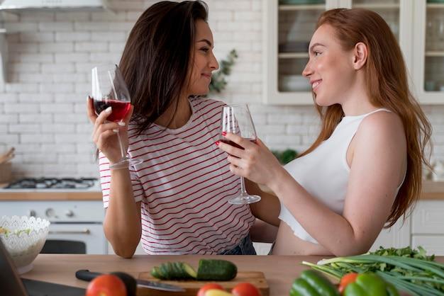 Vrouw geniet van wat wijn tijdens het koken