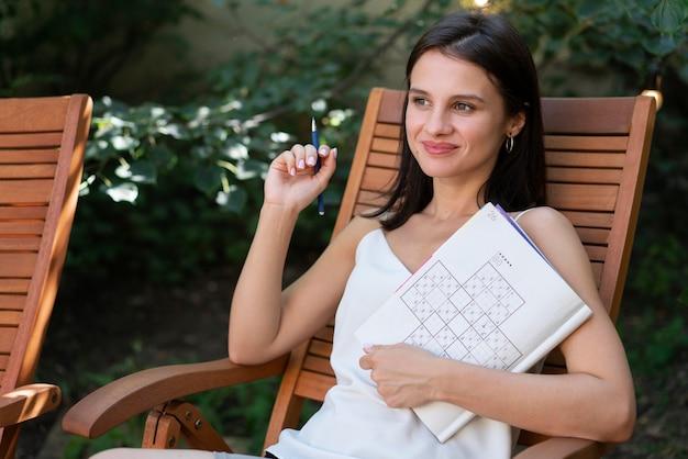 Vrouw geniet zelf van een sudoku-spel op papier