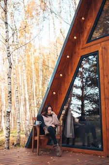 Vrouw genieten in herfstdag op het terras van haar huis