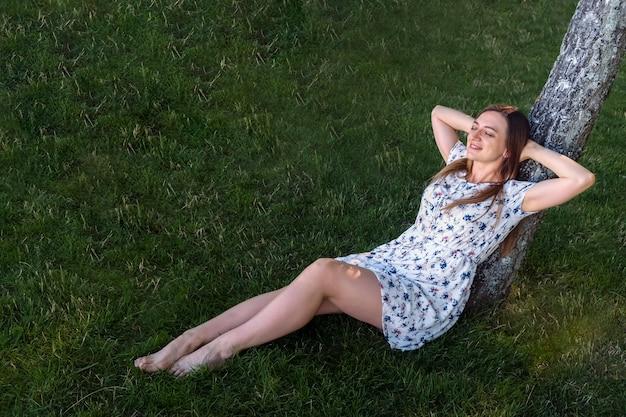 Vrouw genieten met haar handen achter haar hoofd zittend op het gazon haar rug leunend op een boom op zomerdag