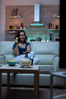 Vrouw genieten van de avond tv-series kijken thuis zittend op een comfortabele bank gekleed in pyjama. opgewonden geamuseerde alleenstaande dame die snacks eet en sap drinkt op een gezellige bank in de woonkamer.