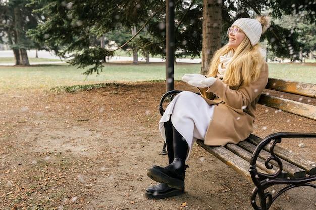 Vrouw genieten van de sneeuwval in het park in de winter