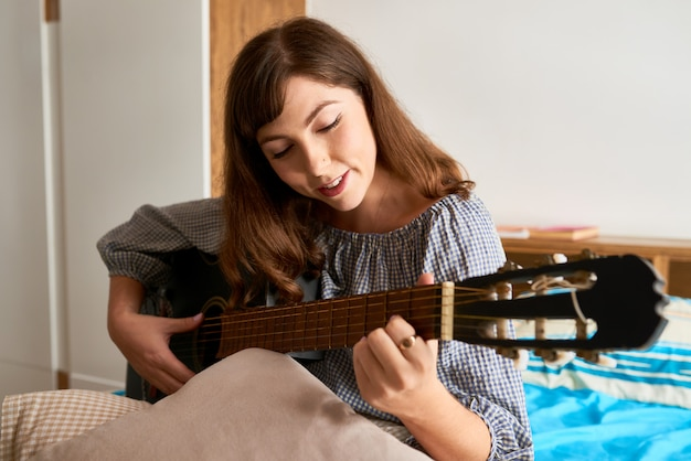 Vrouw genieten van gitaar spelen