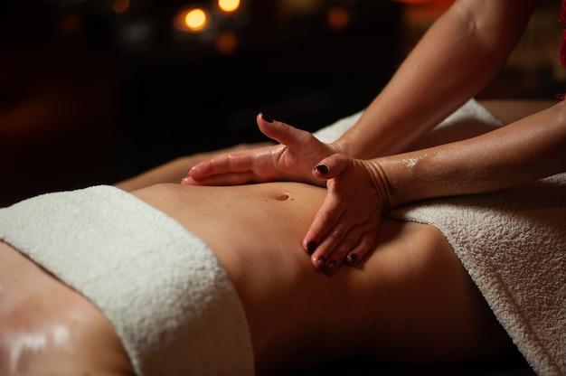 Vrouw genieten van ontspannende rugmassage in cosmetologie kuuroord.