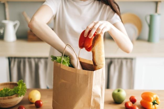 Vrouw genomen groenten uit een papieren boodschappentas in de keuken