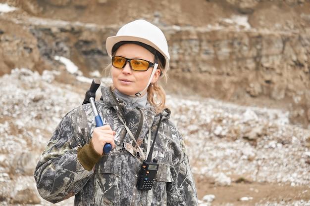 Vrouw geoloog op de achtergrond van de helling van de steengroeve