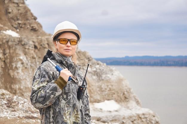 Vrouw geoloog op de achtergrond van de open kuil aan de rand van een berg