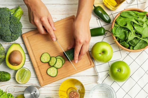 Vrouw gesneden komkommer op witte houten tafel