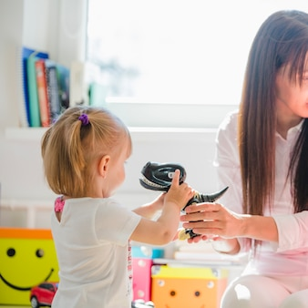 Vrouw geven dinosaurus een meisje weg te kijken