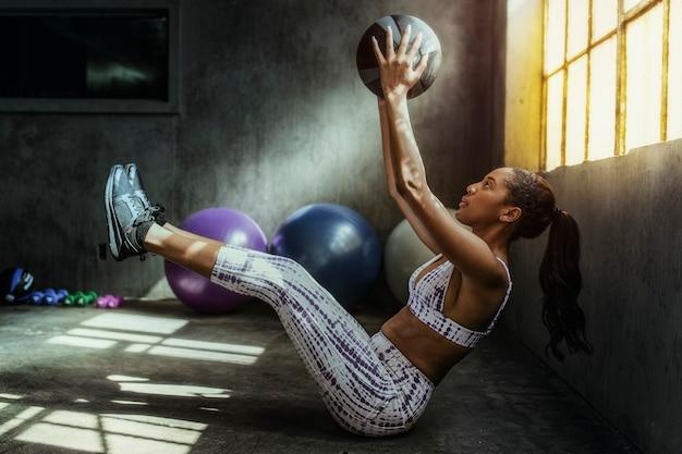 Vrouw gewichtheffen met een medicijnbal in de sportschool