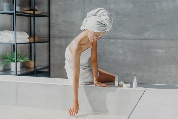 Vrouw gewikkeld in badhanddoek gebruikt cosmetische producten voor de zorg over het lichaam dat een bad gaat nemen