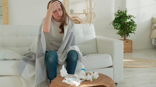 Vrouw gewikkeld in een deken voelt zich ziek met verkoudheid en koorts thuis ziek met griep zittend op de bank