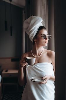 Vrouw gewikkeld in een handdoek koffie drinken