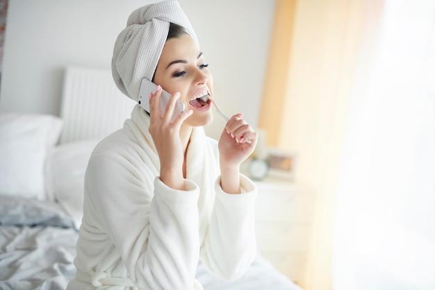 Vrouw gewikkeld in een handdoek met een telefoontje