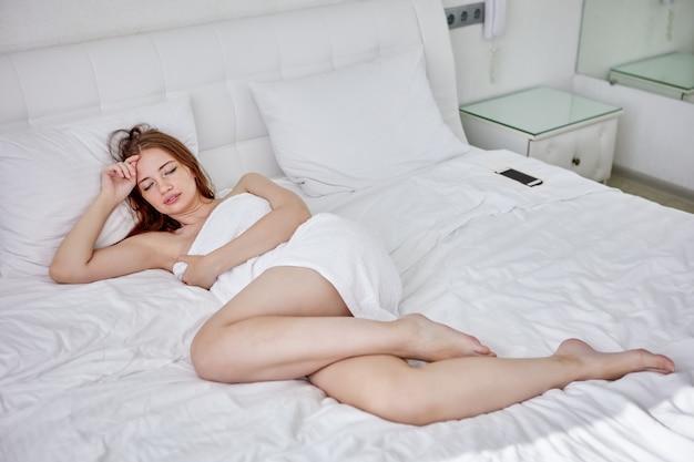 Vrouw gewikkeld in een handdoek rust op bed in de slaapkamer