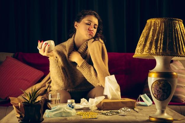 Vrouw gewikkeld in een plaid ziet er ziek, ziek, niezend en hoestend uit als ze binnen zit