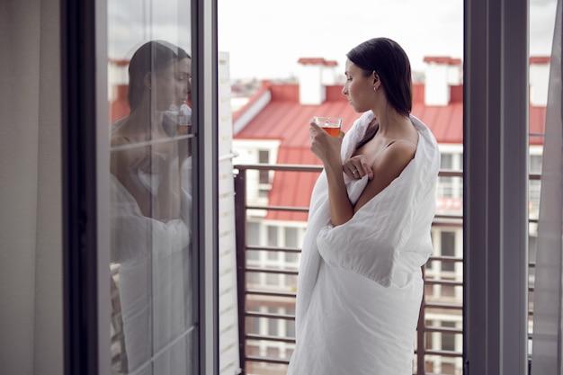 Vrouw gewikkeld in een witte deken staat naast een groot raam, gordijnen drinkt thee uit een mok die zichzelf opwarmt van de kou na een bad
