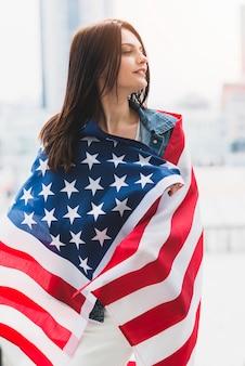Vrouw gewikkeld in sterren en strepen vlag