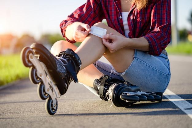 Vrouw gewond knie tijdens skaten. een tiener steekt een blauwe plek met een pleister na het vallen tijdens het inline skaten