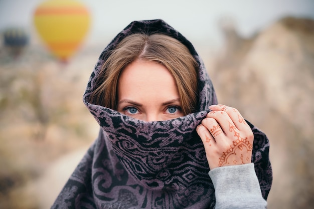 Vrouw gezicht bedekt met sjaal en mehendi tatoeage aan kant