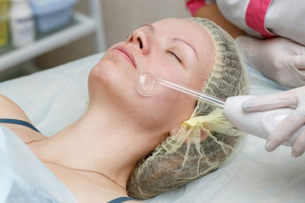 Vrouw gezicht darsonval therapie krijgen bij cosmetologie kliniek