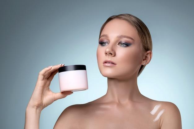 Vrouw gezicht huidverzorging. portret van aantrekkelijke jonge vrouw crème onder ogen toe te passen