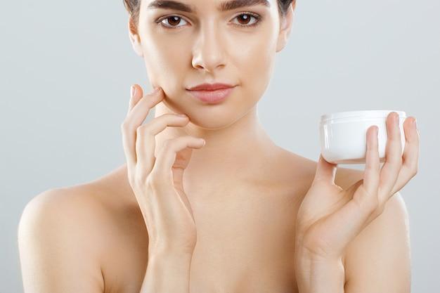 Vrouw gezicht huidverzorging. portret van vrouwelijke holdingsfles