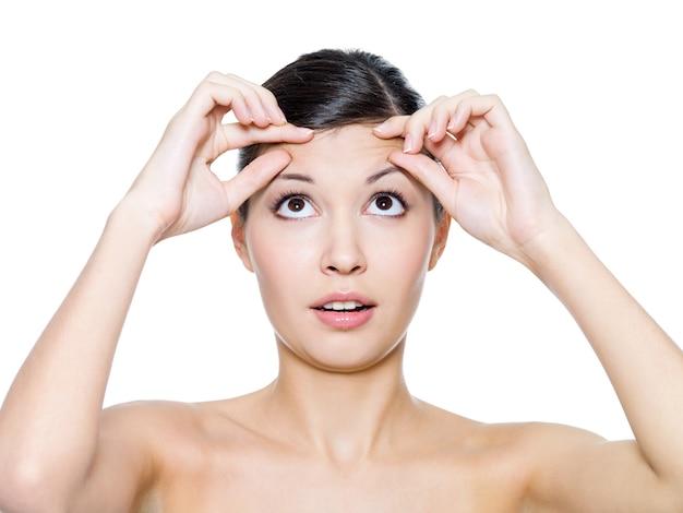 Vrouw gezicht met de rimpels op haar voorhoofd - geïsoleerd op wit