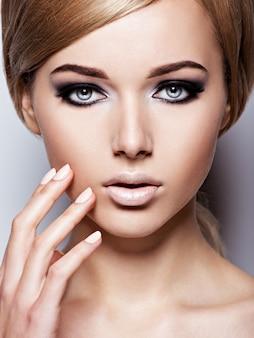 Vrouw gezicht met mode zwarte make-up van oog en lange zwarte wimpers.
