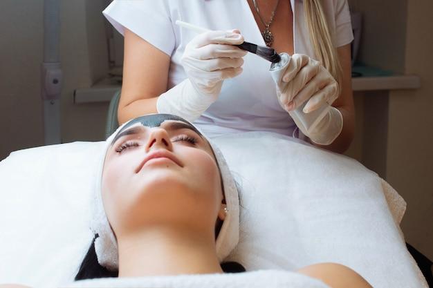 Vrouw gezicht met zwarte handschoenen prachtige vrouw in spa met gezichtsprocedures