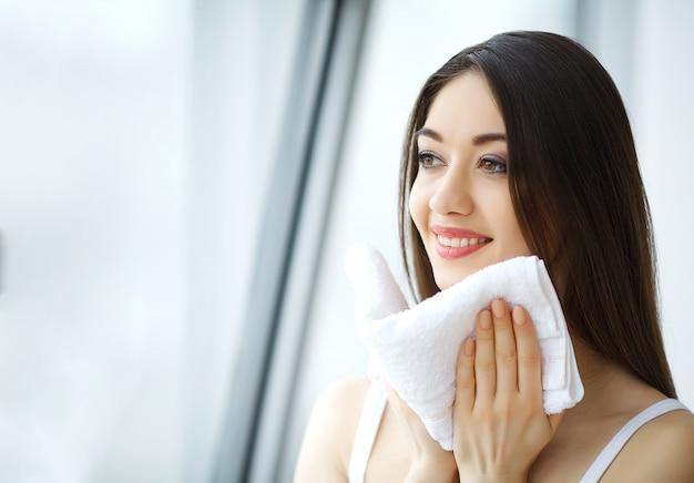 Vrouw gezichtshuid met witte handdoek schoonmaken.