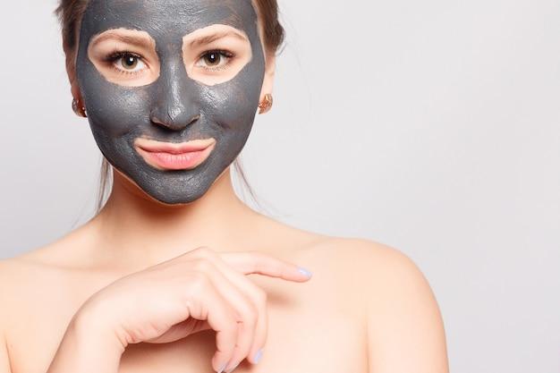 Vrouw gezichtsmasker. portret van mooi meisje cosmetische zwarte peeling masker verwijderen van gezichtshuid. close-up van aantrekkelijke jonge vrouw met natuurlijke make-up en cosmetische peel masker op gezicht. hoge resolutie