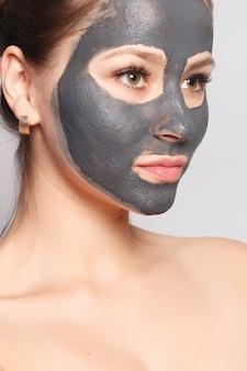 Vrouw gezichtsmasker. portret van mooi meisje dat cosmetische zwarte peeling masker van de gezichtshuid verwijdert. close-up van aantrekkelijke jonge vrouw met natuurlijke make-up en cosmetische peel masker op gezicht. hoge resolutie