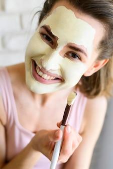 Vrouw gezichtsmasker toe te passen op zichzelf