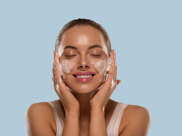 Vrouw gezichtsmasker wassen zeep close-up schone huid. kleur achtergrond blauw