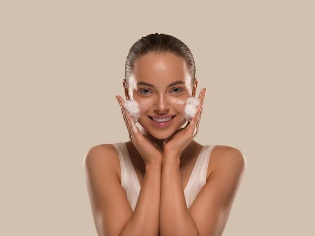 Vrouw gezichtsmasker wassen zeep close-up schone huid. kleur achtergrond bruin