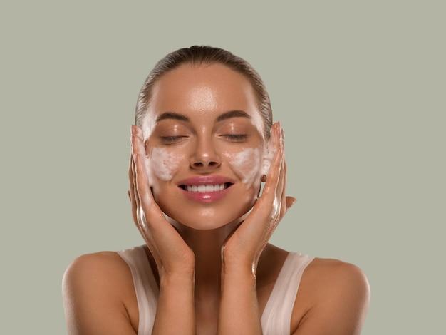 Vrouw gezichtsmasker wassen zeep close-up schone huid. kleur achtergrond groen