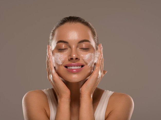 Vrouw gezichtsmasker wassen zeep close-up schone huid. kleur achtergrond