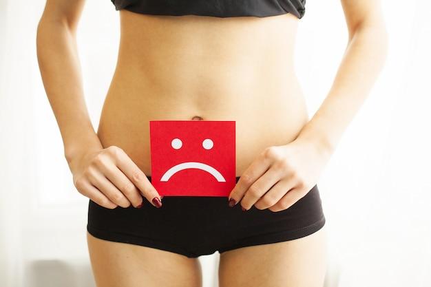 Vrouw gezondheid. vrouwelijk lichaam met droevige smileykaart dichtbij maag