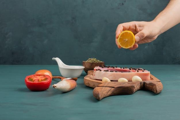 Vrouw giet citroensap in een stuk ongekookt vlees op blauwe tafel.