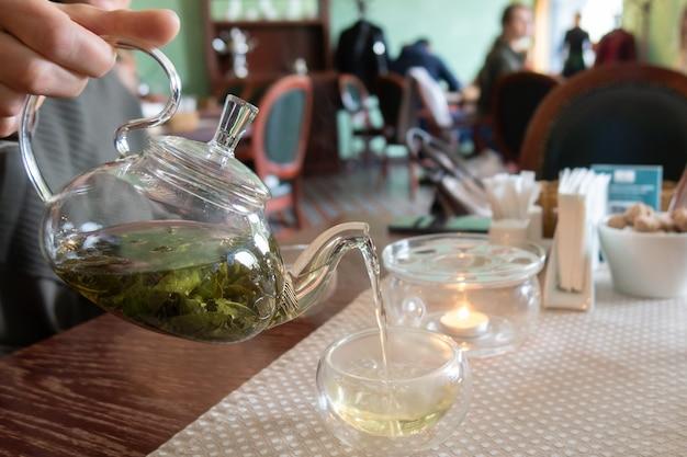 Vrouw giet groene thee uit glazen theepot in
